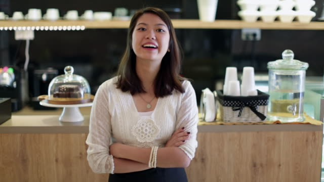 MS Young woman smiling in a café with arms folded.