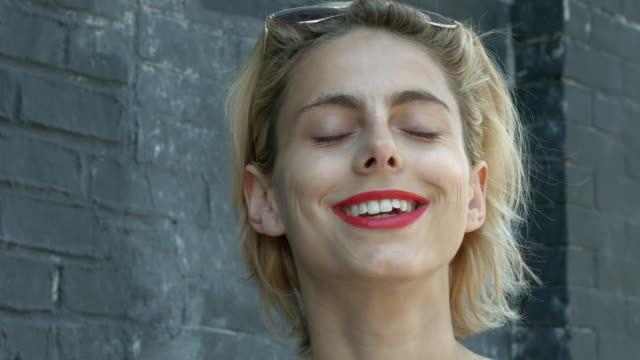 vídeos de stock, filmes e b-roll de a young woman smiling looking at camera outside in new york city - áudio disponível online