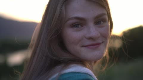 vídeos y material grabado en eventos de stock de ecu young woman smiling outdoors at sunset - chica adolescente
