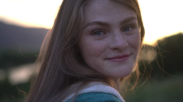 vídeos de stock, filmes e b-roll de ecu young woman smiling outdoors at sunset - menina
