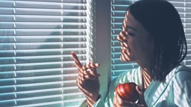 stockvideo's en b-roll-footage met jonge vrouw glimlachend tijdens het eten van een appel en kijkend door het raam - gluren