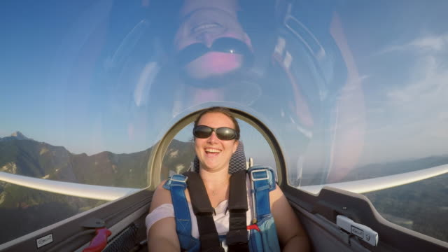 ld young woman smiling while sitting in the back of the glider high in the sunny sky - glider stock videos & royalty-free footage