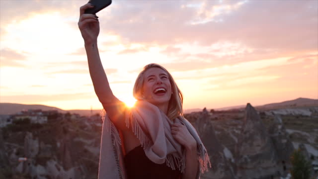 young woman snaps selfie against a desert backdrop, sunset - fascino video stock e b–roll