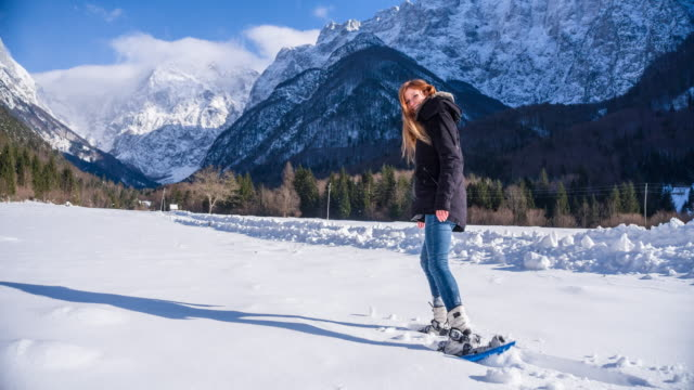 Young woman snowshoeing in the mountainside