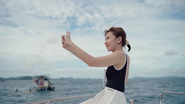 stockvideo's en b-roll-footage met jonge vrouwen soloreis die van het varen bij zonsondergang geniet - zelfportret fotograferen
