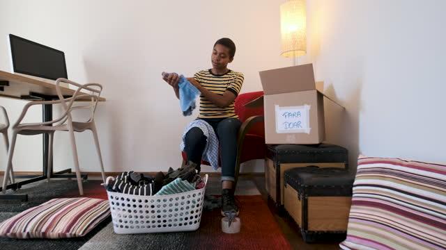 vídeos y material grabado en eventos de stock de mujer joven clasificando ropa para enviarla al servicio social. - sólo mujeres jóvenes