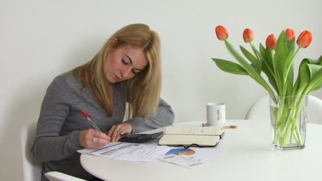 Young woman sorting out her finances, UK