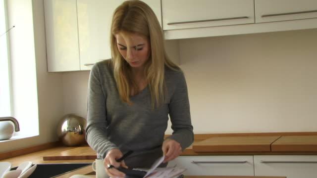 vidéos et rushes de young woman sorting out her finances; uk - seulement des jeunes femmes