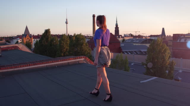 Young woman speaks on her phone on urban rooftop