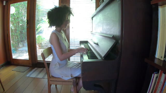 young woman spending a relaxing day in her beautiful home - piano stock videos & royalty-free footage