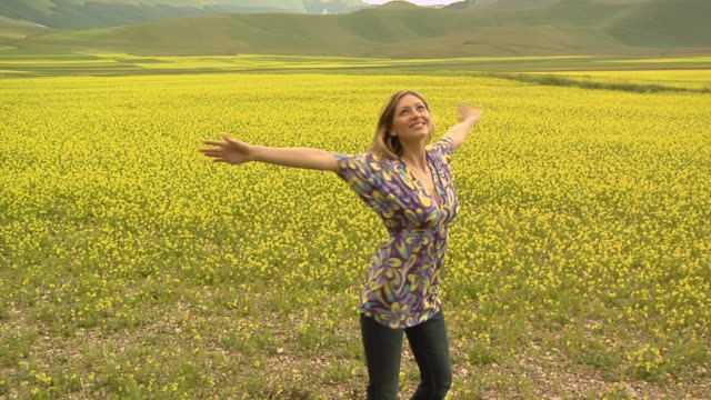 ws zi ms young woman spinning around in field of yellow wildflowers / castelluccio, norcia, italy  - ブラウス点の映像素材/bロール