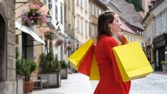 young woman spinning happily with shopping bags in middle of the streeet - shopaholic stock videos & royalty-free footage