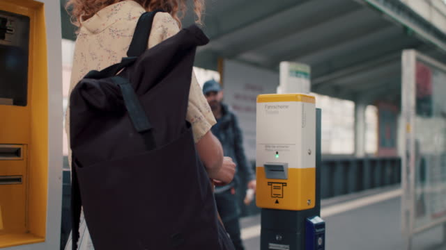 young woman stamping ticket on platform in berlin, germany - punch bag stock videos & royalty-free footage