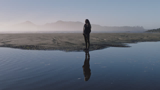 Young woman standing alone on scenic beach is reflected in tidal pool.