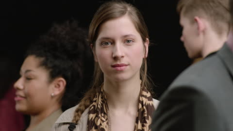 cu young woman standing among walking crowd in slow motion. black background - identity stock videos & royalty-free footage