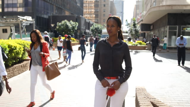 young woman standing at a pedestrian zone in downtown johannesburg. - stadtviertel stock-videos und b-roll-filmmaterial