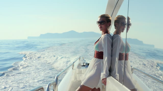 ms young woman standing at rear of luxury yacht / portals nous, mallorca, spain - mode stock-videos und b-roll-filmmaterial