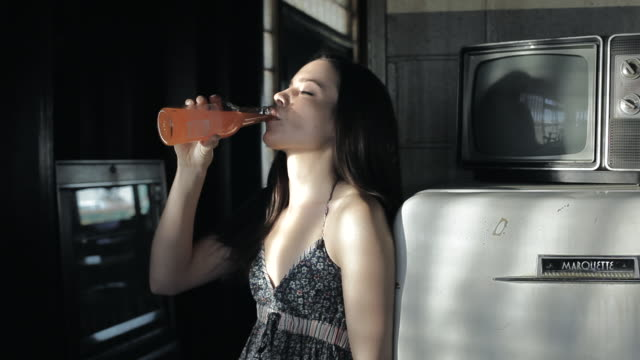 ms young woman standing backwards leaned on fridge, drinking some bevereage in sexy manner / palmdale, ca, united states  - palmdale stock videos and b-roll footage