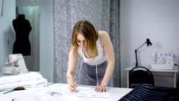 Young woman standing bending over the table in tailoring studio and sketching future dresses. Designer creating new fashion collection. Female dressmaker is working in atelier drawing pattern