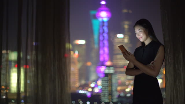 MS young woman standing by a window at night, Shanghai, China