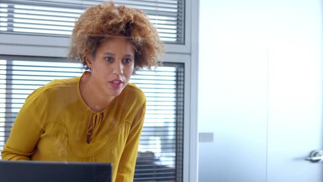 オフィスで机のそばに立ち、同僚と話す若い女性 - 問う点の映像素材/bロール