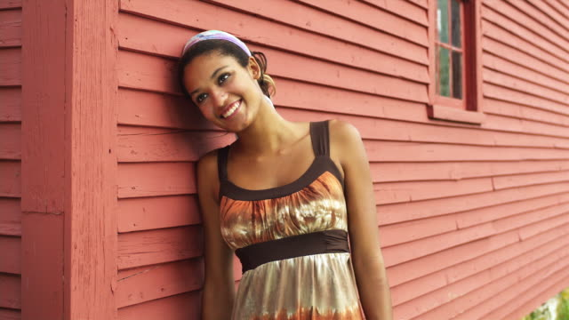 ms young woman standing by red wall, smiling / manchester, vermont, usa - manchester vermont stock videos & royalty-free footage