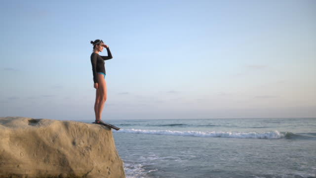 ws young woman standing by the sea, getting ready to snorkel - standing stock videos & royalty-free footage