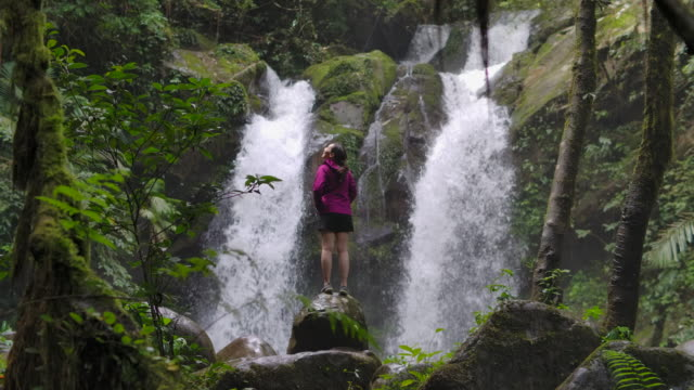 young woman standing by the waterfall and embracing in slow motion - ubud district stock videos & royalty-free footage