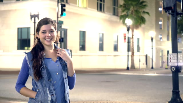 young woman standing in city at night - denim jacket stock videos & royalty-free footage
