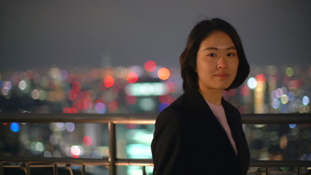 MS Young woman standing in front of a city backdrop at night.