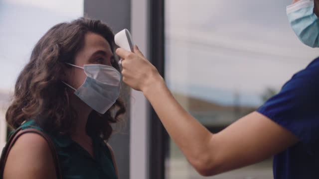 cu young woman standing in medical clinic doorway puts on disposable face mask, uses hand sanitizer, rings doorbell, allows nurse to take her temperature, walks indoors - building entrance stock videos & royalty-free footage