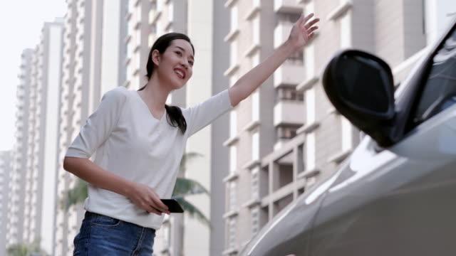 vídeos de stock, filmes e b-roll de mulher nova que está na rua da cidade, prendendo o telefone esperto à disposicão e esperando o táxi ou o uber. tecnologia, pessoas, estilo de vida, conceito de negócios. à espera de um uber - táxi