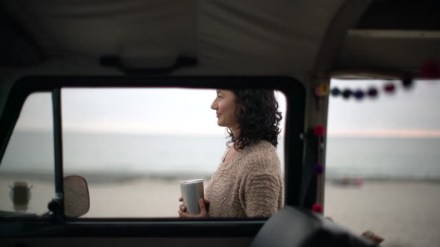 MS Young woman standing near her van drinking coffee