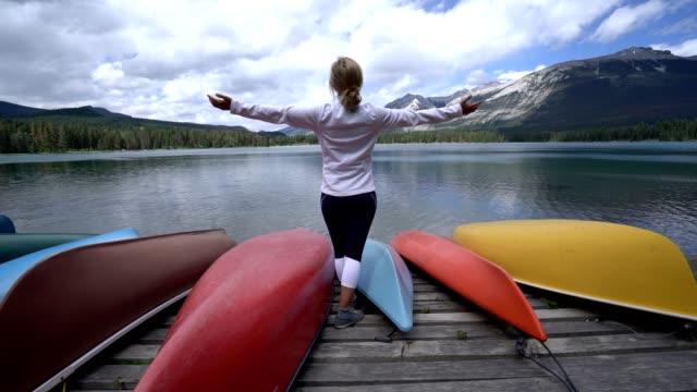 Jonge vrouw stond in de buurt van bergmeer outstretches wapens voor vrijheid, Canada