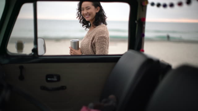 MS Young woman standing next to her vintage camper van