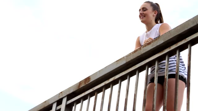 young woman standing on bridge looking around laughing