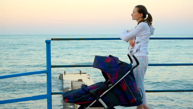 young woman standing on embankment and looking at sea - three wheeled pushchair stock videos & royalty-free footage
