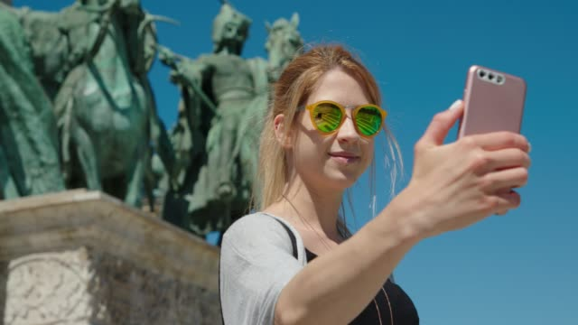 young woman standing on heroes' square and taking a selfie - hungary stock videos & royalty-free footage