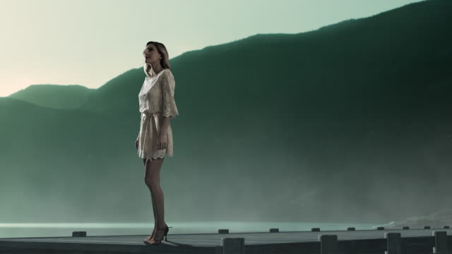 vídeos y material grabado en eventos de stock de young woman standing on jetty - surrealista