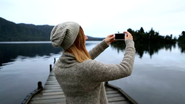 Young woman standing on lake pier taking smartphone picture of landscape