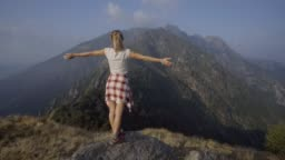 Young woman standing on mountain summit arms wide open enjoying the freshness and success celebrating the achievement feeling free