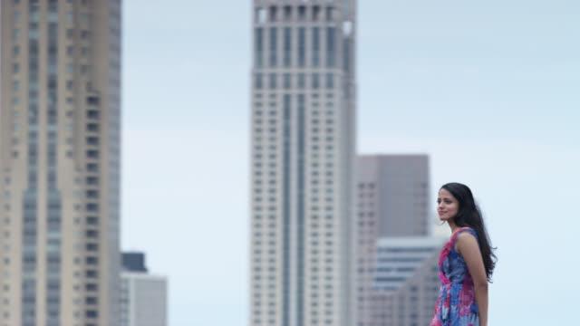 vidéos et rushes de ms pan young woman standing on rooftop, skyscrapers in background, chicago, illinois, usa - seulement des jeunes femmes