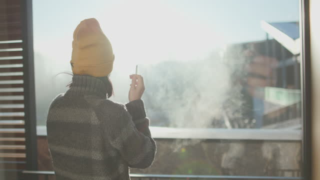 young woman standing on terrace with cap and smoking cigarette - cold temperature stock videos & royalty-free footage