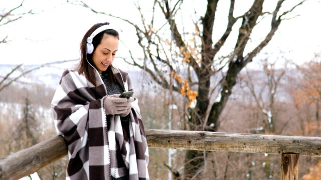 young woman standing on the balcony of a wooden house in snow, listening to music on her headphones - blanket stock videos & royalty-free footage