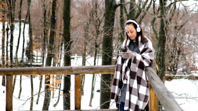 vidéos et rushes de jeune femme debout sur le balcon d'une maison en bois dans la neige, écouter de la musique sur son casque - manteau et blouson d'hiver