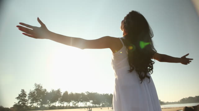 young woman standing on the beach with her arms outstretched  - arms outstretched stock videos and b-roll footage