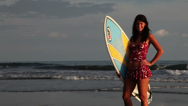 young woman standing on the beach with her surfboard - hand an der hüfte stock-videos und b-roll-filmmaterial