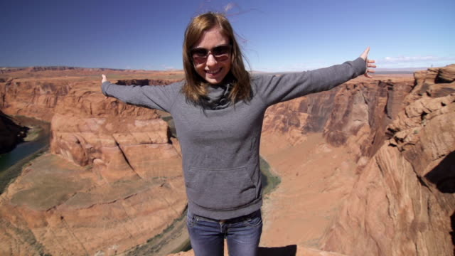 young woman standing on the edge of the grand canyon - grand canyon national park stock videos & royalty-free footage