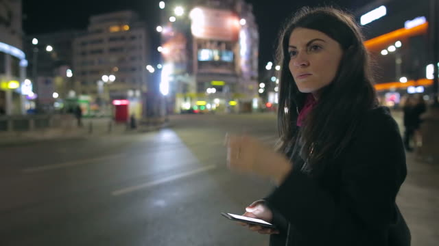 young woman standing on the street and looking at her phone while waiting for uber or taxi. - chauffeur stock videos and b-roll footage