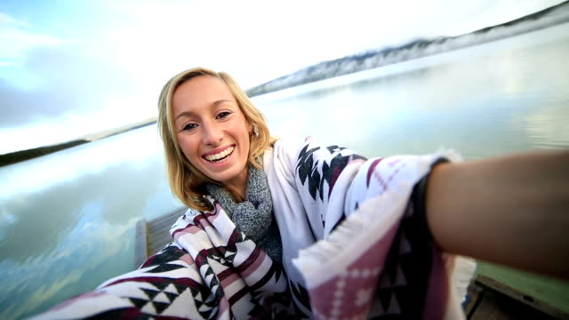 Young woman standing on wooden pier takes selfie portrait